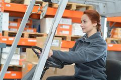 Portrait female fork lift truck driver in factory. Portrait of female fork lift truck driver in factory Royalty Free Stock Images