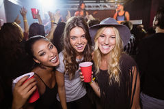 Portrait of female friends with disposable cups in club. Portrait of female friends with disposable cups enjoying music in nightclub Stock Image