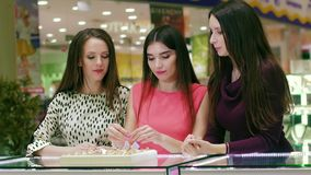 Portrait of female friends in shopping mall looking for a ring stock footage