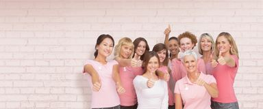 Composite image of portrait of female friends showing thums up sign for breast cancer awareness Stock Photos