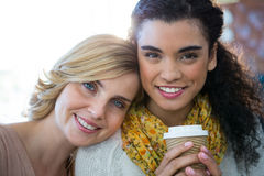 Portrait of female friends sitting together and having coffee. Portrait of smiling female friends sitting together and having coffee in cafeteria Royalty Free Stock Photo
