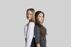 Portrait of female friends standing back to back over white background Stock Photo