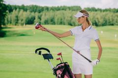 portrait of female golf player in cap with golf gear