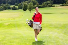 Portrait of female golfer carrying golf bag stock photos
