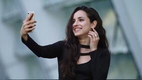 Portrait female having video call outside. Woman touching hair in black dress stock video footage