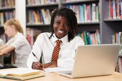 Portrait Of Female High School Student Wearing Uniform Working A. Female High School Student Wearing Uniform Working At Laptop In Library royalty free stock image
