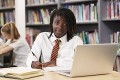 Portrait Of Female High School Student Wearing Uniform Working A. Female High School Student Wearing Uniform Working At Laptop In Library stock image