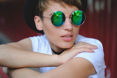 Portrait of female hipster with natural makeup and short haircut enjoying leisure time outdoors Royalty Free Stock Photos