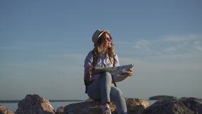 Portrait of female hipster who smiles at the sun and dreams travel. Girl traveler wearing sunglasses and a hat walking down the road in the field. young woman stock video