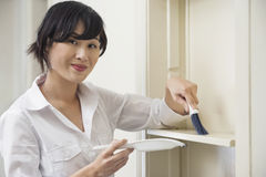 Portrait of female housekeeper cleaning shelf Royalty Free Stock Photography