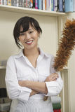 Portrait of female housekeeper holding feather duster Stock Image