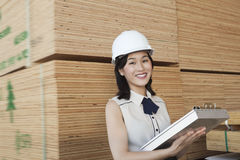 Portrait of female industrial worker holding clipboard with stacked wooden planks in background Stock Photos