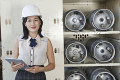 Portrait of female industrial worker holding tablet PC with cylinders on shelf in background Stock Photos
