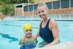 Portrait of female instructor and young boy standing in pool Stock Images