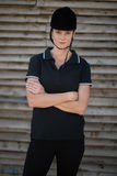 Portrait of female jockey with arms crossed standing by stable Royalty Free Stock Photo