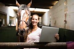 Portrait of female jockey holding laptop while standing by horse. Portrait of smiling female jockey holding laptop while standing by horse in stable Royalty Free Stock Images