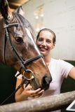 Portrait of female jockey by horse. Standing in stable Stock Photo