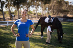 Portrait of female jockey with sister by horse in background. At paddock Royalty Free Stock Photo