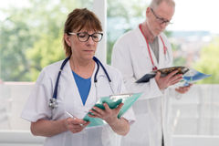 Portrait of female and male doctors. Portrait of female and male mature doctors Stock Image