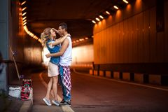 Portrait of female and male skaters embrace passionately, going to kiss, stand against tunnel background, recreat after. Active skateboarding in open air Stock Photo