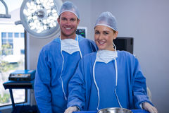 Portrait of female and male surgeon standing in operation theater. At hospital Stock Photography