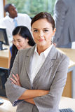 Portrait Of Female Manager In Busy Office. Crossing Her Arms Stock Photography