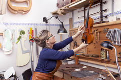 Portrait of female mature violin maker. While testing the violins in his laboratory Stock Image