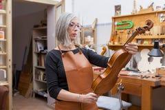 Portrait of female mature violin maker Stock Photos