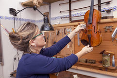 Portrait of female mature violin maker while testing the violins Stock Photos