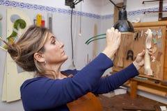 Portrait of female mature violin maker royalty free stock image