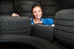 Portrait of a female mechanic,surrounded by car tyres Royalty Free Stock Image
