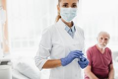 Young doctor in protective mask standing in hospital room royalty free stock photography