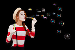 Portrait of the female MIM comedian blows soap balls. Isolated on black background Stock Photos