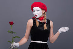 Portrait of female mime with red hat and white. Waist-up portrait of female mime with red hat and white face pretty smiling and looking at the camera while Royalty Free Stock Photography