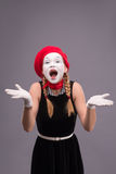 Portrait of female mime in red head and with white Stock Photos