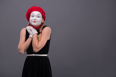Portrait of female mime with white funny face. Waist-up portrait of female mime with surprised face, red hat and red scarf looking at the camera smiling and Stock Photography