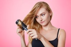 Portrait of female model combs her light straight hair, going to have date with boyfriend, cares about her hair, prepares to make royalty free stock photography