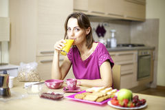 Portrait of female model drinking murice. Beautiful woman in pajamas having breakfast with fresh fruit cereals buiscuits and orange juice Stock Image