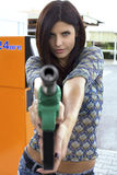 Portrait of female model holding and pointing gas gun Stock Images