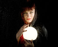 Portrait of female model, posing behind transparent glass covered by water drops. woman holding large glowing ball Royalty Free Stock Photo
