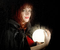 Portrait of female model, posing behind transparent glass covered by water drops. woman holding large glowing ball Stock Photography