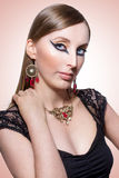 Portrait. Female model posing with black eyeliner and jewelry with red stones Royalty Free Stock Photography