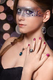 Portrait. Female model posing with a makeup strip across the eyes, purple droplets and jewelry with green and blue stones Stock Images
