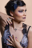 Portrait. Female model posing with purple eyeliner and jewelry with metals decorations Stock Image