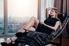 Portrait of female model wearing short black dress and high heels relaxing on chair.  Stock Photography