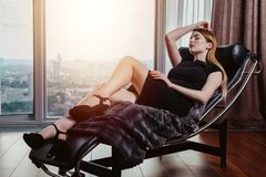 Portrait of female model wearing short black dress and high heels relaxing on chair.  Royalty Free Stock Image
