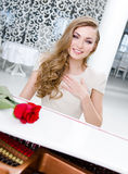 Portrait of female musician with red rose playing piano Stock Photo