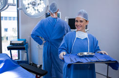 Portrait of female nurse holding surgical tray in operation theater. At hospital Royalty Free Stock Photo