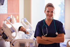 Portrait Of Female Nurse With Patient In Background Stock Photo