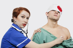Portrait of female nurse treating an injured male patient against gray background Stock Images
